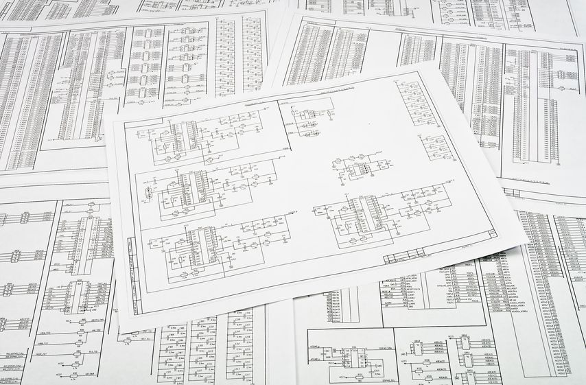 Background of several electrical circuit diagrams printed on multiple sheets of paper
