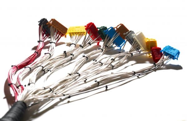 Wire harness loom with multiple coloured connectors at each end isolated on a white background