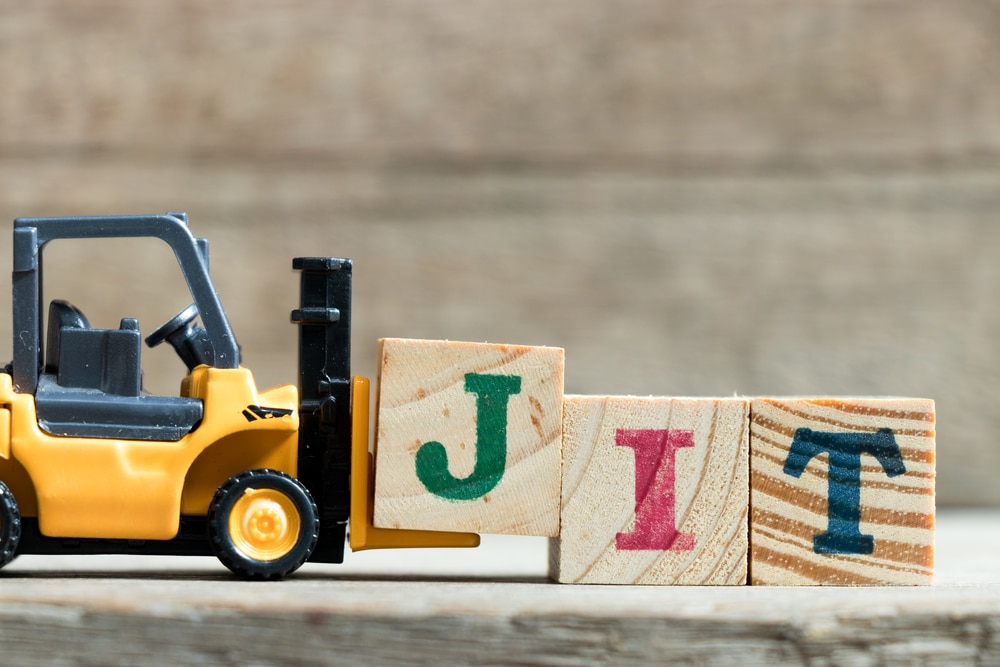 Toy yellow forklift holding a letter block J to complete word JIT (abbreviation of Just In Time) on wood background